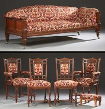 Austrian Five Piece Carved Mahogany Parlor Suite, c. 1900, consisting of a settee, two armchairs and two side chairs, the chairs wit...
