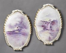 Pair of French Porcelain Plaques, early 20th c., of oval shield form, with enhanced transfer decoration of a woman in a boat and a m...
