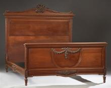 French Carved Walnut Louis XVI Style Double Bed, c. 1900, the arched headboard with an elaborate floral crest over a stepped top abo...