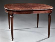 French Louis XVI Style Carved Mahogany Dining Table, c. 1900, the rectangular top over a wide skirt on turned tapered fluted legs to...