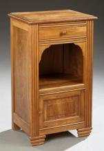 French Art Deco Carved Walnut Nightstand, early 20th c., the inset rectangular top over a frieze drawer above an open shelf above a...