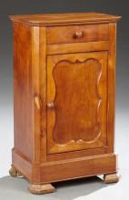French Louis Philippe Carved Cherry Nightstand, 19th c., the canted corner rectangular top over a frieze drawer above a cupboard doo...