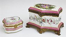 Two French Porcelain Brass Mounted Dresser Boxes, one 19th c., of shaped form with hand painted floral decoration, the lid with a sc...