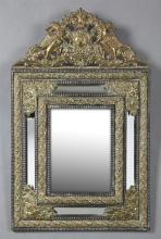 French Renaissance Style Brass Repousse Cushion Mirror, c. 1880, with a winged gryphon and shield crest over a segmented mirror arou...