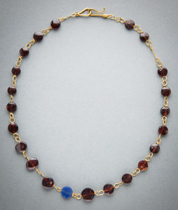 Imperial roman gold necklace wrapped with garnet disc beads and a single opaque blue glass bead