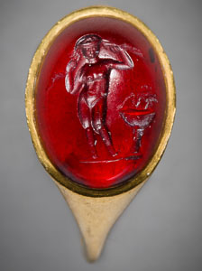 Hellenistic Greek gold ring with cabochon garnet intaglio of Aphrodite, nude, standing by a fountain and arranging her hair