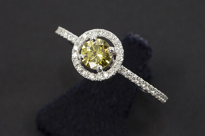 ring in white gold (18 carat) with a central yellow fancy color high quality brilliant of 052 carat and ca 040 carat of very high quality brilliant