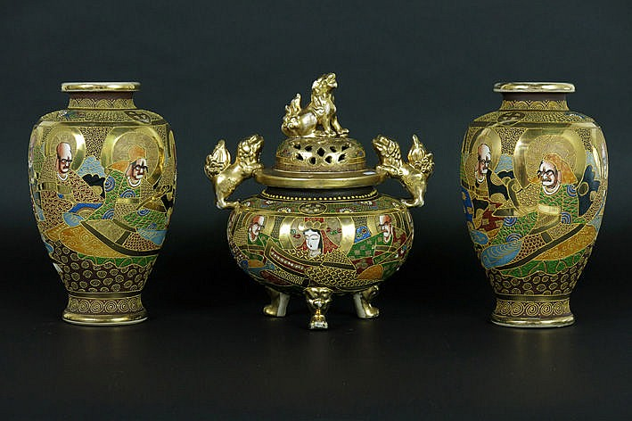Japanese three-piece garniture in Satsuma earthenware with typical decor: pair of vases and incense burner