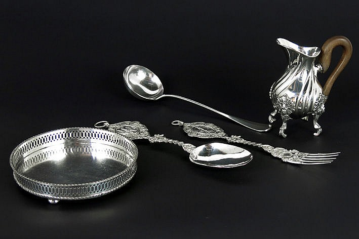 five items in marked silver with a round dish table cutlery a ladle and a small jug on four legs