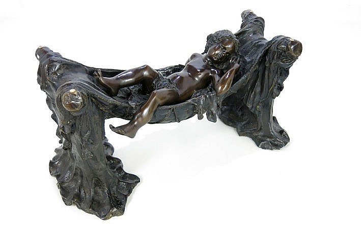 fancy table with a glass top on a quite large sculpture in bronze
