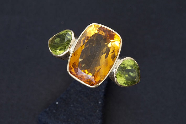 handmade design ring in yellow gold (18 carat) with a central topaz of ca 650 carat and 2 pearshaped peridots together ca 5 carat