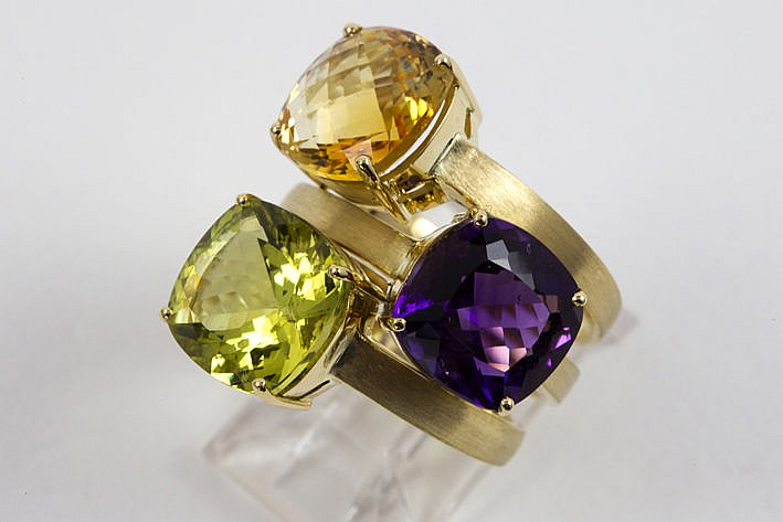 3 modern handmade rings (�) in yellow gold (18 carat) one with a peridote one with an amethyste and one with a yellow topaz - together weighing ca 19 carat