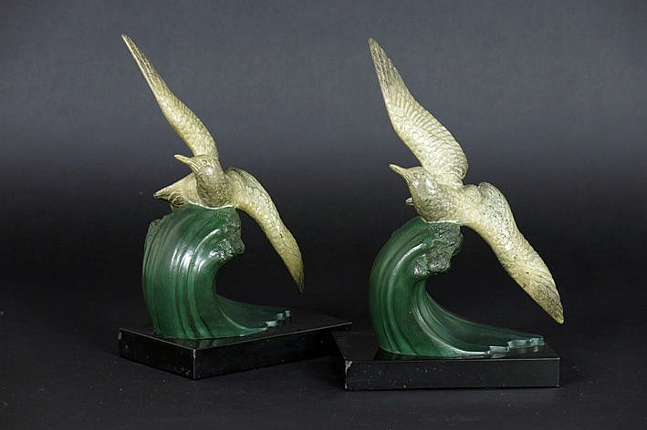 pair of (�) bookends in black marble each with a cold painted sculpture