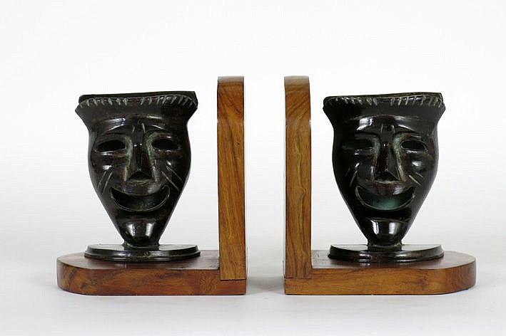 pair of (�) bookends in walnut each with a mask with a smiling face in bronze