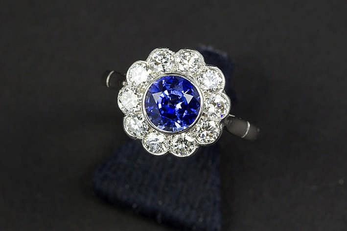 Aantrekkelijke ring in platina met een bloemvormig sierestuk met een zeer mooie Ceylon- saffier van ca 1 60 karaat omringd door ca 1 karaat blauwwitte (F) kwaliteitsbriljant (Vvs)