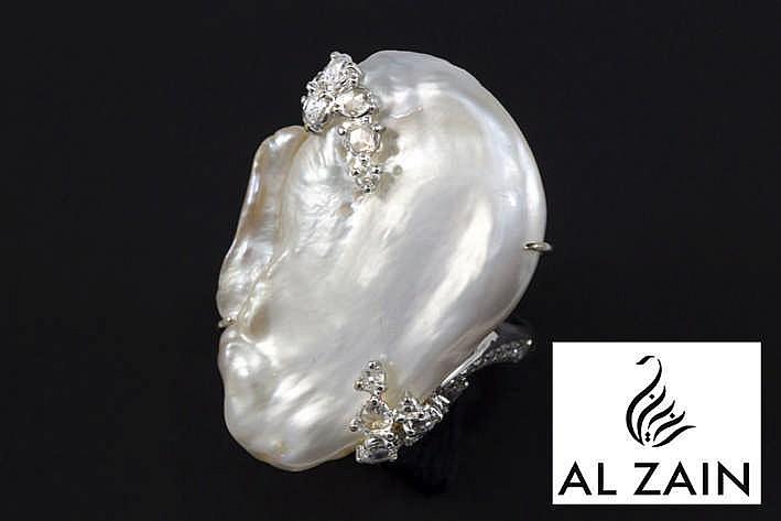 AL ZAIN (top juwelier van Dubai) zeer aparte design ring in witgoud (18 karaat) met een sierstuk met een organische vorm bezet met een grote (3 5 cm) wilde (natuurlijke) parel en met ca 0 70 karaat blauwwitte (D/E/F) loepzuivere/Vvs diamant in de