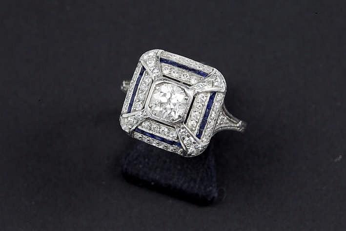 Mooie Art Deco-ring in platina met een fijnbewerkte corpus en met een piramidaal sierstuk centraal bezet met een witte (G) briljant (Si) in oude slijp van ca 0 60 karaat omringd door drie banden twee bezet met brilj in achtkant en één met saffier -
