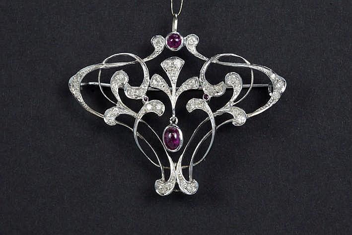 Sierlijke broche met een typisch Art Nouveau-model in grijs goud (18 karaat) bezet met ca 0 80 karaat robijn in cabochonslijp en ca 0 70 karaat diamant
