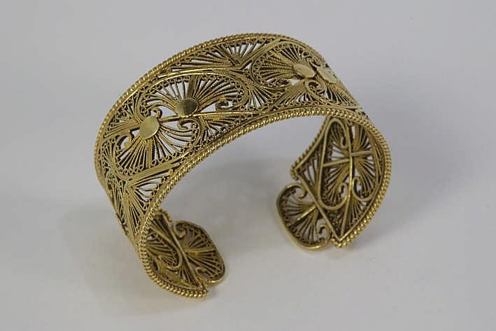 Bracelet met een vrij breed zgn esclavemodel met geajoureerde band met fijn filigranenwerk - in geelgoud (18 karaat) - 62 3 gram