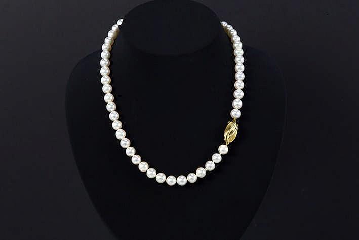 Vrij lang collier met één rij op de witte kleur en grootte (diameter : ca 10 mm) gezochte parels met zeer mooie luster en met een ovaal dubbelzijdig slot in deels gematteerd geelgoud (18 karaat)