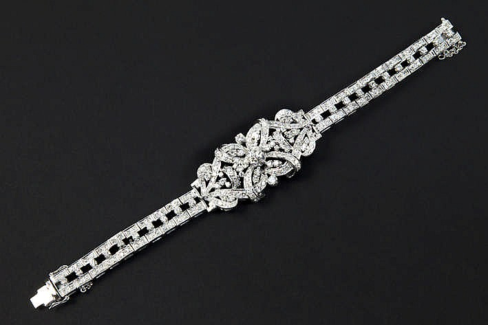 Vrij uitzonderlijk bracelet in witgoud (18 karaat) met een schakelband bezet met briljant en met een sierstuk bezet met een centrale briljant van ca 0 80 karaat omringd door kleinere - in totaal : ca 10 60 karaat witte (D tot G) briljant (Si/P) - met