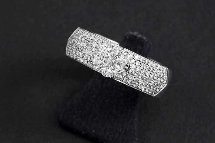 Fijn gerealiseerde ring in witgoud (18 karaat) met ind e corpus gezette briljant en met een rond sierstuk beet met briljant - in totaal : ca 1 15 karaat blauwwitte (E/F) kwaliteitsbriljant (Vs) - 6 7 gram
