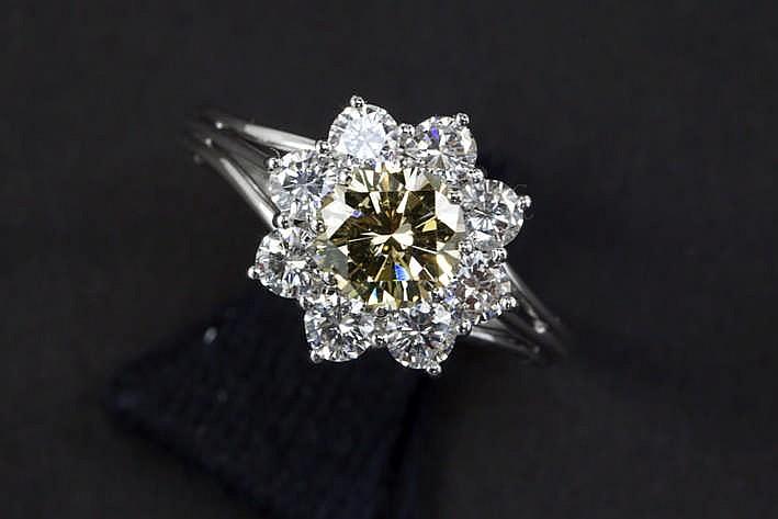 Ring in wit goud (18 karaat) met een fancy color-briljant (Si) van 1 16 karaat met natuurlijke cognackleur omringd door ca 1 karaat witte (G) kwaliteitsbriljant (Si)