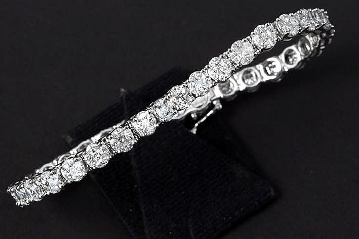 Schitterend bracelet in witgoud (18 karaat) met een apart rivièremodel met rondom bloemvormige schakels bezet met ca 12 karaat blauwwitte (F) kwaliteitsbriljant (Vvs) in princesse- en marquiseslijp