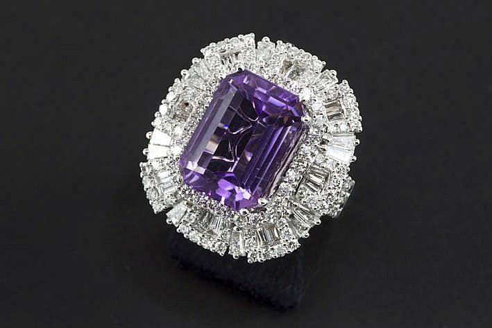 Klassevolle ring in witgoud (18 karaat) met een apart entouragemodel centraal bezet met een amethyste van 9 à 10 karaat omringd door een band briljant en een bredere band met briljant en diamant in teperslijp - in totaal : zeker 2 50 karaat witte