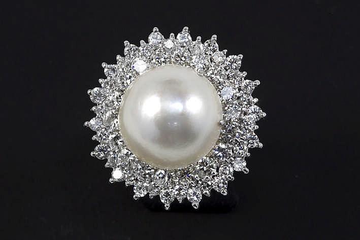 Klassevolle ring in witgoud (18 karaat) met een rond entouragemodel centraal bezet met een Mabé-parel van 16 5 mm omringd door ca 4 karaat witte (F/G/H) briljant (Vs/Si/P)