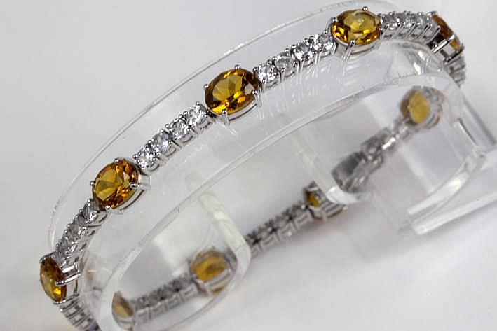 Fijn bracelet met rivièremodel in witgoud (18 karaat) rondom bezet met ca 5 20 karaat witte saffier afgewisseld met ca 9 50 karaat ovaalgeslepen topazen met fraaie zgn 'keizerlijke' kleur