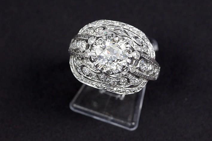 Solitaire briljant (J - Vs) van 1 63 karaat in oude slijp omringd door ca 1 karaat witte (H) briljant (Si) gezt in een ring met typisch Art Deco-model in grijs goud (18 karaat)
