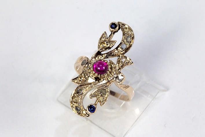 Vrij speciale ring in geelgoud (18 karaat) met een rocaillevormig sierstuk bezet met een robijn in cabochonslijp saffier en diamant