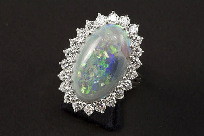 Mooie ring in witgoud (18 karaat) met een ovaal sierstuk centraal bezet met een opaal (2 1 x 1 8 cm groot) omringd door ca 1 80 karaat witte (F/G) kwaliteitsbriljant (Vvs/Vs) - 9 gram