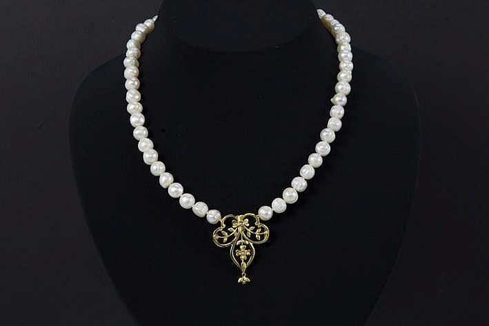 Collier met één streng op de kleur gezochte witte barokke parels en met een fraai pendatief en slot in geelgoud (18 karaat) telkens bezet met pareltjes