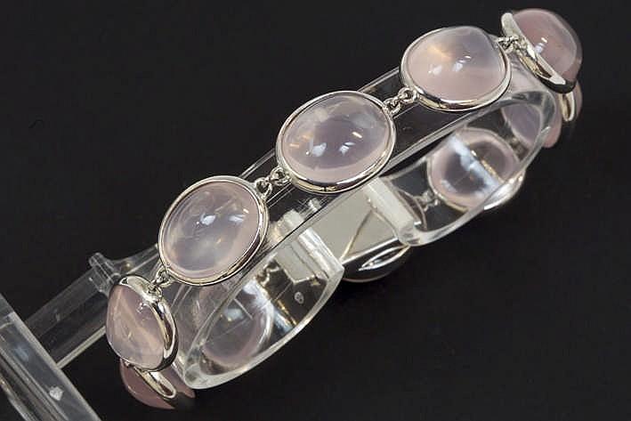 Met de hand gerealiseerd designbracelet in witgoud 18 met rondom ovale schakels telkens bezet met een roze kwarts in cabochonslijp - in totaal zeker 63 karaat roze kwarts