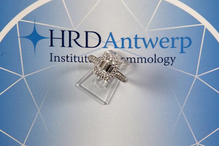 Klassevolle ring in witgoud (18 karaat) met een rechthoekig sierstuk bezet met een witte (H) kwaliteitsbriljant (Vs1) van 1 56 karaat in smaragdslijp omringd door ca 0 80 karaat witte (G) kwaliteitsbriljant (Vs) met certificaat HRD voor de solitaire