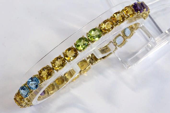 Superb volledig met de hand gerealiseerd en modieus bracelet met een zogenaamd 'rivière' - model in geelgoud 18 rondom bezet met ovale edelstenen in pastelkleuren: zeker 15 karaat topaas ca 4 karaat amethyste en ruim 1 50 karaat peridoot