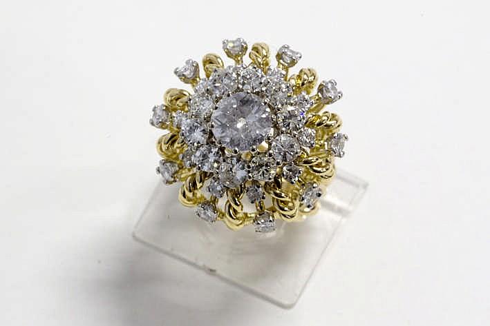 Aparte Franse ring met een karakteristiek seventies' zgn princessenmodel in geel en witgoud (18 karaat) met kroonvormig sierstuk centraal bezet met een witte (F/G) briljant (P) van ca 1 50 karaat omringd door ca 3 karaat witte (G/H/I) briljant