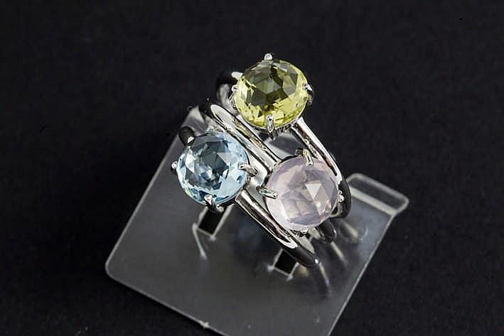 Set van drie (apart of gecombineerd te dragen) ringen in witgoud (18 karaat) telkens met een solitaire kleuredelsteen in brioletslijp één met rose quartz één met citroengele en één met blauwe topaas