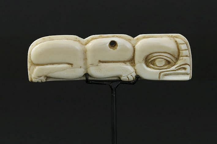 CANADA/NOORD-WESTELIJKE KUST - 19° EEUW fraaie amulet van een Haïda- of Tiglit- sjamaan in ivoor van een walvis (whaleross of spermwhale) met een sterk gestileerde voorstelling - breedte : 7 5 cm - gemonteerd uit een Engelse collectie ref :