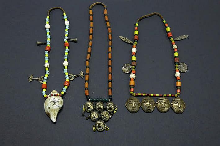 BIRMA - NAGALAND drie unieke halskettingen gemaakt van zeer oude kralen in glas(pasta) waarvan één met een schelp en twee met bronzen hoofdjes (verwijzend naar de gesnelde koppen)