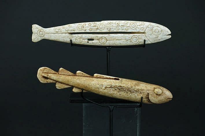 ALASKA/INUIT - 20° EEUW lot met twee Eskimo-amuletten in walvissenbeen met de vorm van een vis met fijnuitgewerkte ornamentiek - werden genaaid op de kleren van de vissers om een goede vangst te verzekeren - breedte : 12 1 en 12 8 cm - telkens
