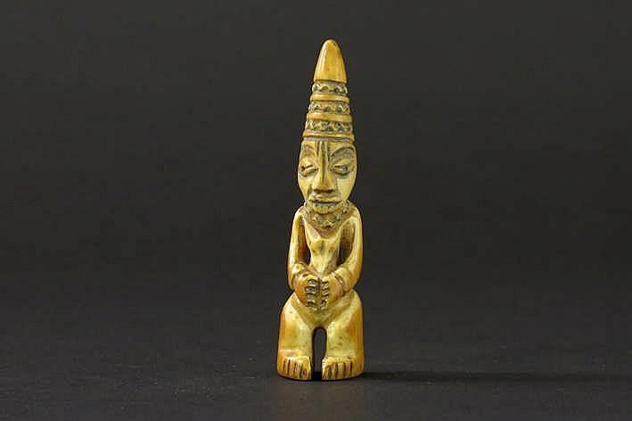 AFRIKA/KONGO ietwat aparte 'Lega' - sculptuur in ivoor en in de vom van een staande vrouw met kegelvormig hoofddeksel en met typische corpus en gelaat - hoogte : 8 5 cm uit de Belgische collectie (Oostende) ref : 'White Gold Black Hands' van Marc