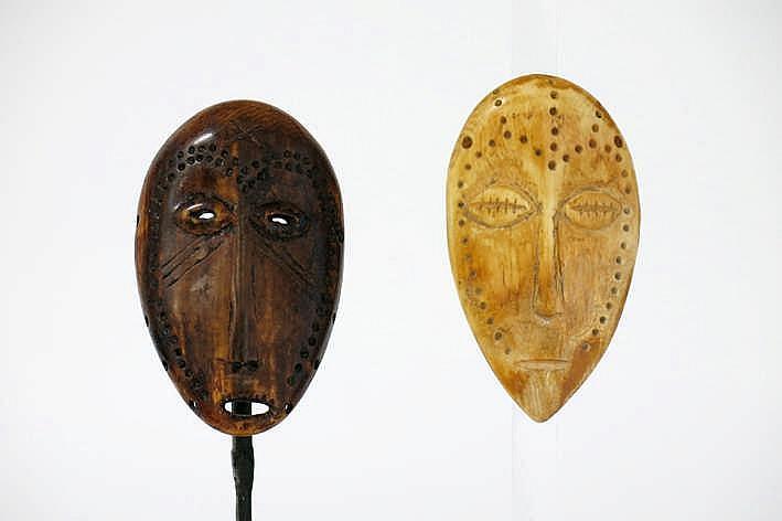 AFRIKA/KONGO 2 'Lega' - maskers in ivoor met typische vorm ogen en neus en telkens met scarificaties - hoogte : 10 5 en 10 4 cm uit de Belgische collectie ('De Saffer') ref : * 'Joyeux Lega' van Baeke * catalogus 'Arts de Lega' - Museum Quai Branly -