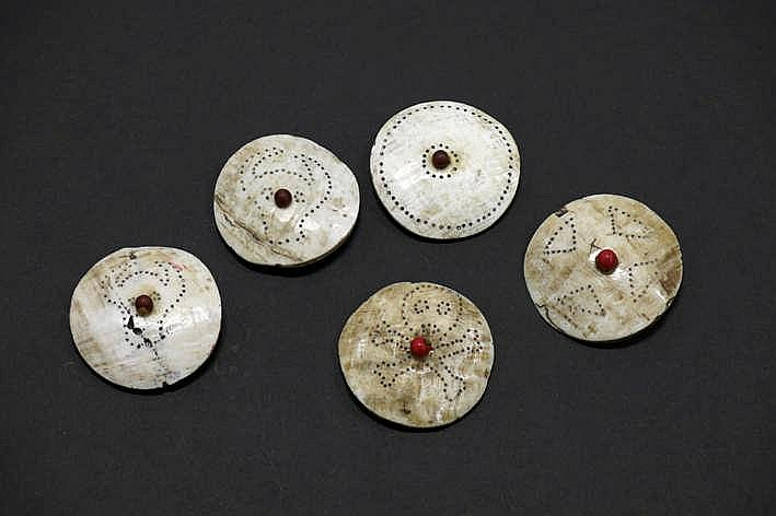 BIRMA - NAGALAND - eind 19° EEUW lot van vijf zgn 'Naga'-knopen sjamanistische amuletten in been met gesculpteerde ornamentiek en met centraal een rode kraal