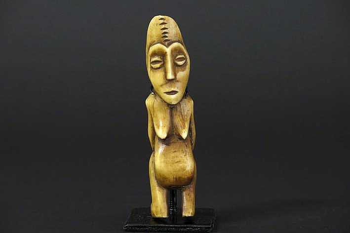 AFRIKA/KONGO - 20° EEUW (of vroeger) 'Lega' -materniteitsbeeldje in mooi gepatineerde ivoor met de voorstelling van een vrouw met dikke buik hangende borsten typische amandelvormige ogen in een ovaal gezicht met scarificaties en met de armen