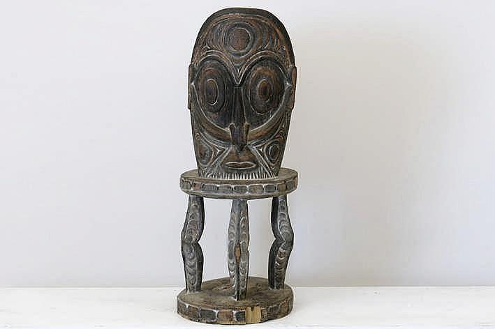 PAPOEASIE NIEUW-GUINEA / MIDDEN-SEPIK - 20° EEUW rituële Sepik 'orator'-stoel in hout met restanten van de originele polychromie met karakteristiek gesculpteerde ornamentiek met op de rug een masker met een gestileerd menselijk gelaat - hoogte : 83