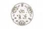 Assiette à bord contourné en faïence de Moustiers à décor en camaïeu vert de grotesques et d'animaux fantastiques sur trois terrasses entourées de fleurs et feuillages. XVIIIème siècle. D. : 25,5 cm.