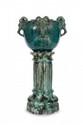 Clément Massier (1845-1917) et Jérôme Massier (1850-1916) Cache-pot sur colonne (complet) en céramique verte nuancée comprenant un cache-pot modèle « Faunes » signé et situé Golf Juan et une sellette modèle « Colonne ». H. : 96 cm. Bibliographie :
